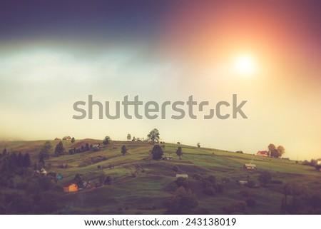 Beautiful sunshine at misty morning landscape in mountain village. Filtered image:cross processed vintage effect.  - stock photo
