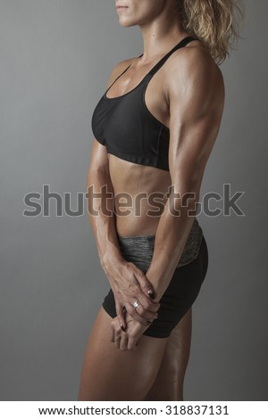 Beautiful super fit young woman showing off her perfect muscular body. Fitness model. Perfect Slim Body with sturdy triceps. Studio shot - stock photo