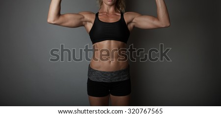 Beautiful super fit young woman showing off her perfect muscular ripped abs and biceps's. Fitness model. Perfect Slim Body. Studio shot - stock photo