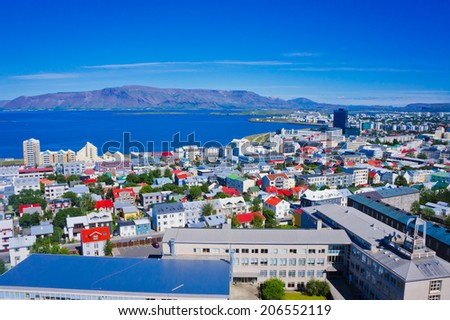 Beautiful super wide-angle aerial view of Reykjavik, Iceland with harbor and skyline mountains and scenery beyond the city, seen from the observation tower of Hallgrimskirkja Cathedral,  - stock photo