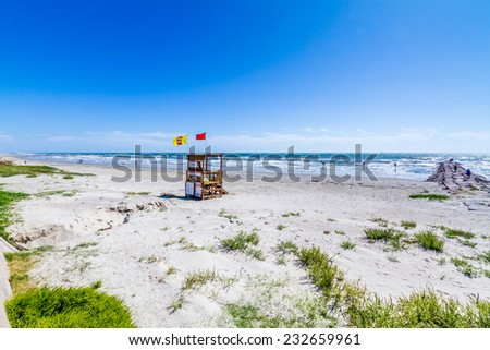 Beautiful Surf and Sand on a Summertime Ocean Beach Holiday Vacation with a Lifeguard Station. - stock photo