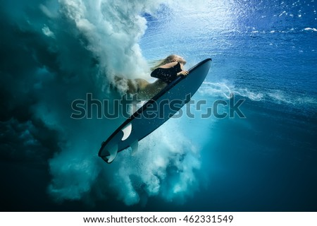 Beautiful Surfer Diving Duckdive under Big Ocean Wave. Turbulent air bubbles and tracks after sea wave crashing. Ripples at water surface with sky color.