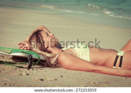 Beautiful Surfer Girl lying on the Beach at the day time