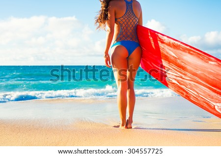 Beautiful Surfer Girl on the Beach at Sunset. Summer Fun Outdoor Lifestyle. - stock photo