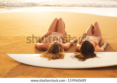 Beautiful Surfer Girls on the Beach at Sunset - stock photo