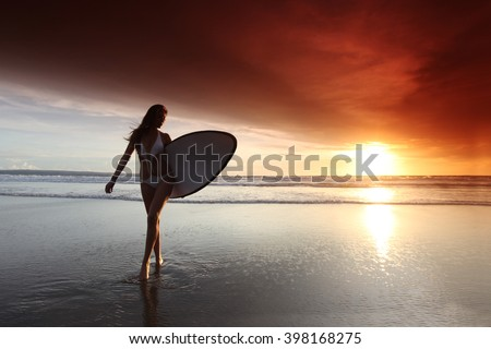 Beautiful surfer woman on the beach at sunset - stock photo