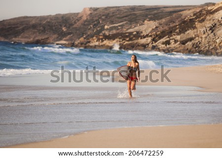Beautiful surfist running on the beach with  her surfboard - stock photo