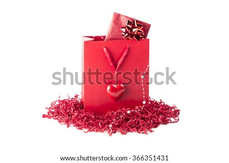 Beautiful surprise present bag with a symbol of love heart. Wonderful red gift with a card inside, maybe voucher or concert tickets for Valentine's Day or Mother's Day. Isolated on white background
