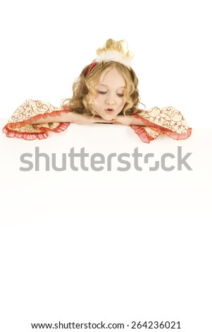 Beautiful surprised little girl with long blonde hair in the princess costume looking down the sign - stock photo
