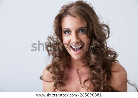 Beautiful surprised smiling young woman with healthy long curly hair