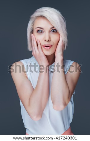 beautiful surprised woman isolated against gray background