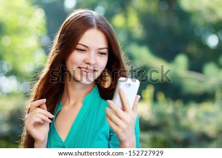 beautiful surprised young woman using mobile - stock photo