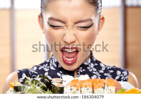 Beautiful sushi woman showing a plate of sushi. - stock photo