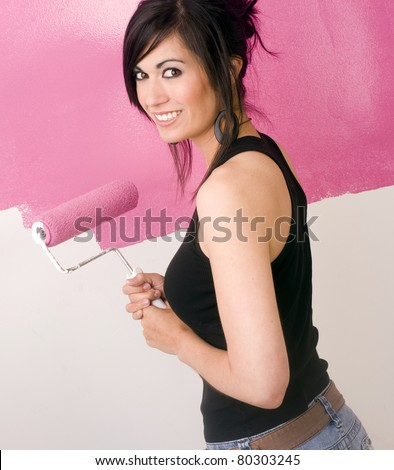 Beautiful Suzy Homemaker Woman Painting a Room Pink DIY Project Holding Paint Roller - stock photo