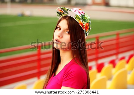 beautiful swag girl posing on the football stadium