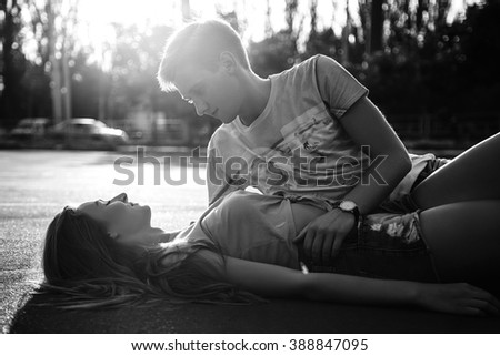 Beautiful sweet couple lying on the asphalt  and hugging on the street during sunset. Black and white - stock photo