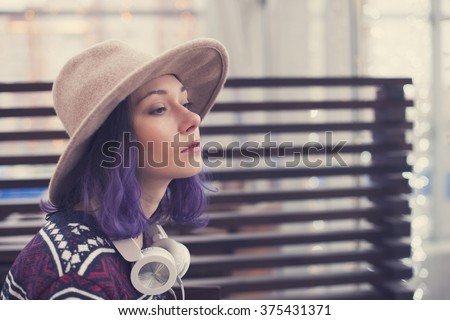 Beautiful sweet girl with blue hair, white headphones and hat looking ahead in anticipation of something. - stock photo