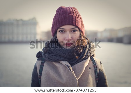 Beautiful sweet girl with red lips posing against the backdrop of the River Neva in St. Petersburg. - stock photo