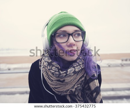 Beautiful sweet girl with violet hair, glasses, green hat, coat and scarf listening to music on headphones white against the backdrop of the frozen Gulf of Finland in St. Petersburg.