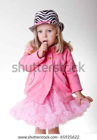 Beautiful sweet toddler girl in pettiskirt and zebra hat - stock photo