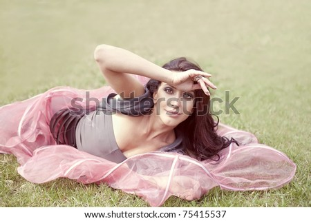 beautiful sweet woman in a pink dress on the green grass in the park - stock photo