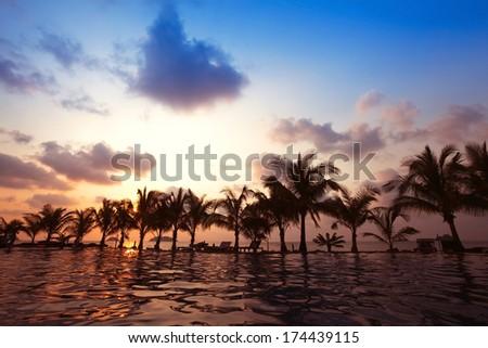 beautiful swimming pool near the beach by sunset - stock photo