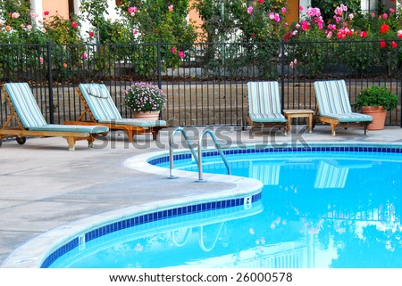 beautiful swimming pool surrounded by chairs and flowers - stock photo