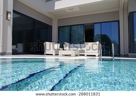 Beautiful swimming pool with white outdoor furniture on modern luxury resort - stock photo