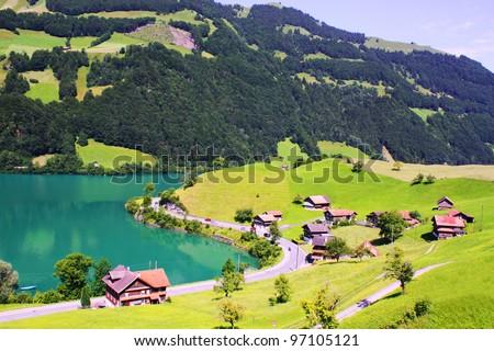Beautiful Switzerland landscape with houses, lake and mountain - stock photo