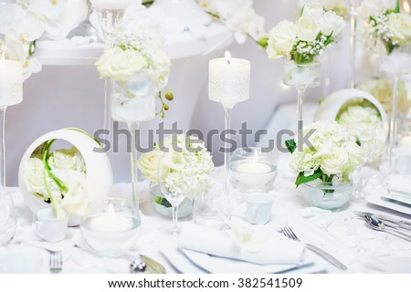 Beautiful table set with candles and flowers for a festive event, party or wedding reception - stock photo