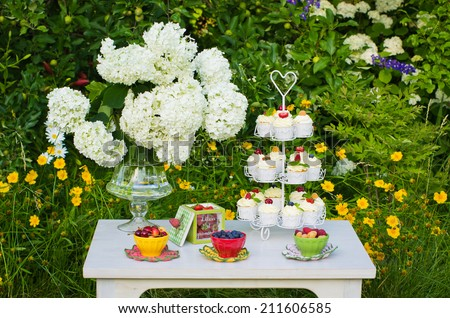 Beautiful table with mascarpone cupcakes, fresh berries and flowers, set in a summer garden - stock photo