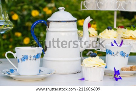 Beautiful table with mascarpone cupcakes, vintage teapot and cups and flowers, set in a summer garden - stock photo