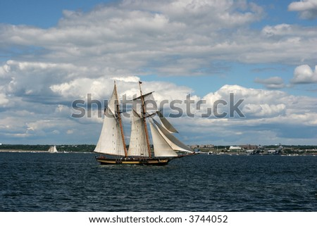 beautiful tall ship on ocean with blue sky and white puffy clouds - stock photo