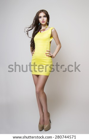 beautiful tall woman with perfect hair  and bright yellow dress - stock photo