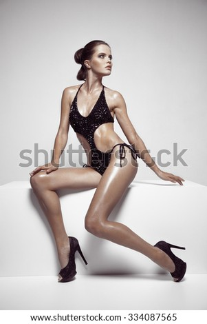 Beautiful tan female model posing in bikini and shoes. Against white wall. - stock photo