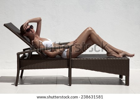 Beautiful tan female model sunbathing in bikini on chaise-longue. Against white wall. - stock photo