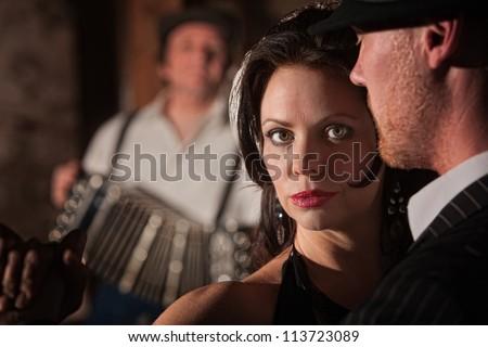 Beautiful tango dancer with partner and accordion musician - stock photo