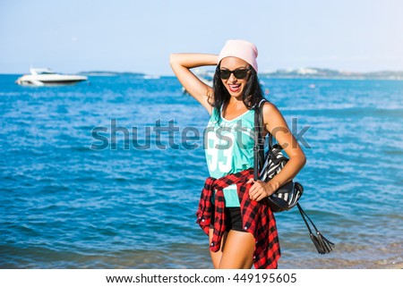 Beautiful tanned cheerful funny cheeky hipster girl on the beach, sea, ocean, enjoying the sun, dressed in casual clothes, denim shorts, plaid shirt, pink hat, striped backpack, crazy emotions - stock photo