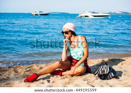 Beautiful tanned cheerful funny cheeky hipster girl traveling, on the beach, sea, ocean, enjoying the sun, sitting on the sand dressed in casual clothes, a plaid shirt, a pink cap, striped backpack - stock photo