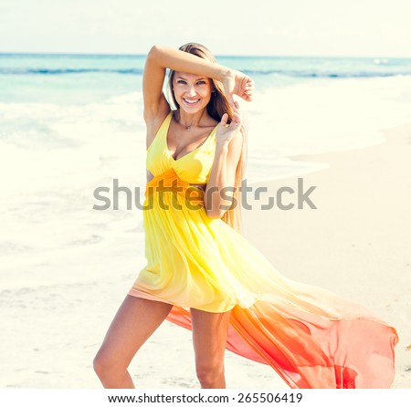 Beautiful tanned fashion sexy girl in glamorous dress posing on the beach on her amazing vacation - stock photo