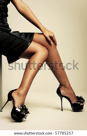 beautiful tanned female lags in high heels, studio shot - stock photo