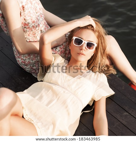beautiful tanned girl in yellow summer dress with a to-go cup lies on her girlfriend's knee on wooden bridge under water - stock photo