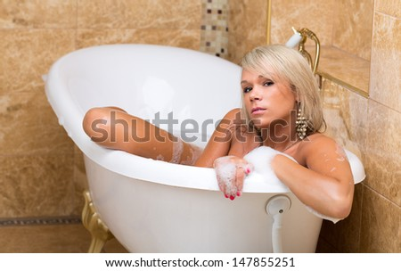 Beautiful tanned girl is taking a luxurious bubble bath.