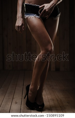 Beautiful tanned legs of young woman on wooden background