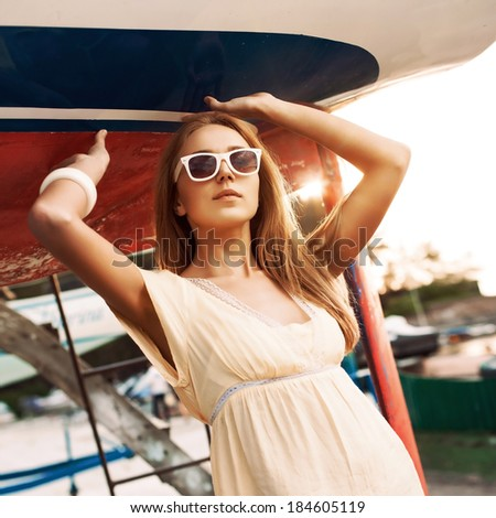 beautiful tanned sexy ginger girl in yellow summer dress and sunglasses stands under blue-and-red boat in sun rays - stock photo