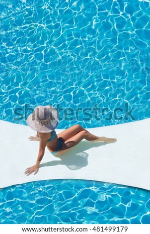 beautiful tanned sporty slim woman relaxing in swimming pool spa.