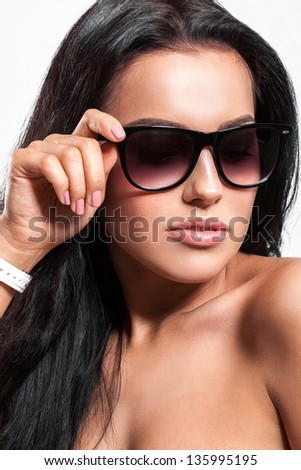 Beautiful tanned woman in sunglasses - stock photo