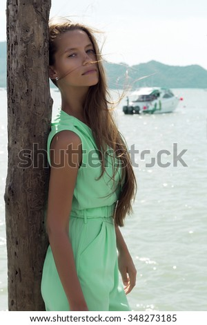Beautiful tanned woman on pier in stylish elegant clothes poses enjoying amazing view. Fashion look. Phuket island, Thailand - stock photo