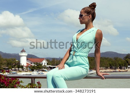 Beautiful tanned woman on pier with hair up in black sunglasses and stylish elegant clothes poses enjoying amazing view. Fashion look. Phuket island, Thailand - stock photo