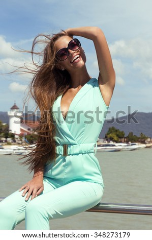 Beautiful tanned woman on pier with hair waving by wind in black sunglasses and stylish elegant clothes poses enjoying amazing view. Fashion look. Phuket island, Thailand - stock photo